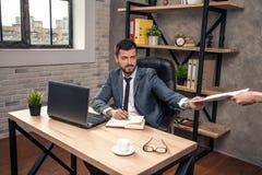 O homem de negócios considerável à moda novo em sua mesa no escritório está obtendo alguns documentos de seu secretário imagem de stock