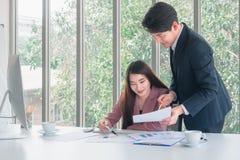 O homem de negócios considerável asiático no suporte do terno dos azuis marinhos para explicar detalhes do trabalho à mulher de n foto de stock royalty free