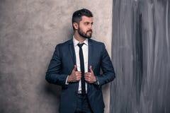 O homem de negócios considerável bonito está estando em no seu escritório e pensamento terno vestindo e um laço imagem de stock