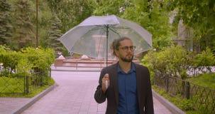 O homem de negócios considerável do moderno anda com guarda-chuva que sorri na câmera que é positiva no parque vídeos de arquivo