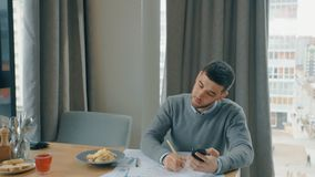 O homem de negócios considerável está trabalhando com o projeto, guardando o telefone que senta-se na tabela do café vídeos de arquivo