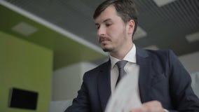 O homem de negócios considerável lê um embarque do jornal e da espera no plano filme