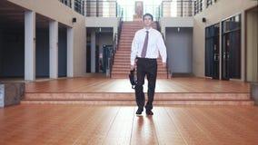 O homem de negócios considerável novo em um terno anda com uma pasta em um businesscentre Uma comunicação, contatos, um novo cont video estoque