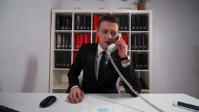 O homem de negócios considerável pede que você espere e precise algumas suas perguntas pelo telefone vídeos de arquivo
