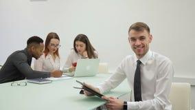 O homem de negócios considerável sorri ao ler o relatório em sua tabuleta na sala detrabalho filme