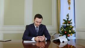 O homem de negócios considerável texts a mensagem de SMS a sua esposa bonita que usa um telefone celular antes do Natal vídeos de arquivo
