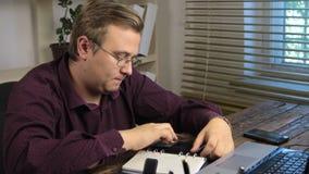 O homem de negócios conta em uma calculadora e escreve em um bloco de notas video estoque