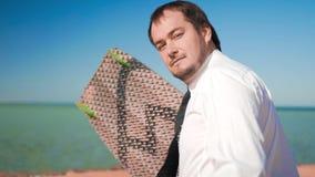O homem de negócios corre ao mar com uma placa do kitesurf filme
