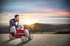O homem de negócios corre com seu carro na estrada fotografia de stock