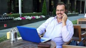 O homem de negócios da Idade Média trabalha no portátil video estoque