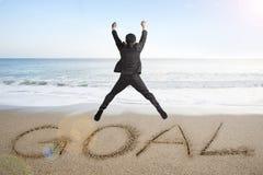 O homem de negócios de salto que cheering para o objetivo exprime escrito na praia da areia Fotografia de Stock