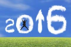 O homem de negócios de salto que cheering a seta 2016 acima da forma nubla-se com gra Imagens de Stock