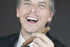 O homem de negócios de sorriso prende o charuto Fotografia de Stock Royalty Free