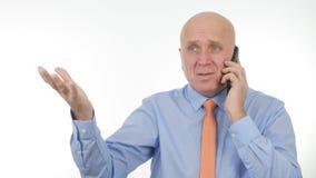 O homem de negócios decepcionado Talk Bad News no telefone celular faz gestos de mão nervosos fotografia de stock