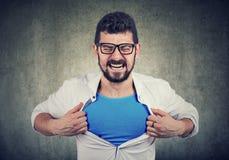 O homem de negócios desesperado para a mudança desabotoa sua camisa e transformar-se um superman imagens de stock