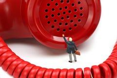O homem de negócios diminuto está na frente de um telefone Fotografia de Stock Royalty Free