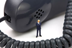 O homem de negócios diminuto está na frente de um telefone Imagens de Stock Royalty Free