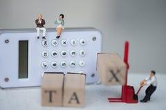 O homem de negócios diminuto senta-se na calculadora para pensa o ano fiscal do rendimento anual do pagamento fotos de stock