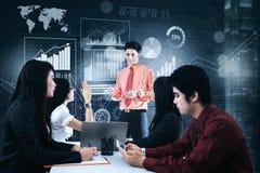 O homem de negócios discute gráficos da finança com seus sócios Imagem de Stock Royalty Free