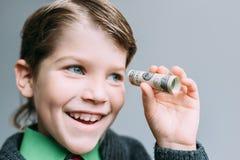 O homem de negócios do menino olha através do tubo pequeno do dólar Fotos de Stock
