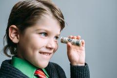 O homem de negócios do menino olha através do tubo pequeno do dólar Fotos de Stock Royalty Free