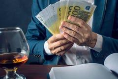 O homem de negócios do homem no terno põe o dinheiro em seu bolso Um subôrno sob a forma das contas do Euro Conceito da corrupção Foto de Stock
