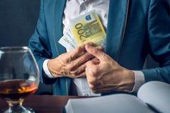 O homem de negócios do homem no terno põe o dinheiro em seu bolso Um subôrno sob a forma das contas do Euro Conceito da corrupção Fotos de Stock Royalty Free