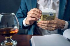 O homem de negócios do homem no terno põe o dinheiro em seu bolso Um subôrno sob a forma das contas do Euro Conceito da corrupção Imagens de Stock