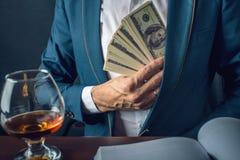 O homem de negócios do homem no terno põe o dinheiro em seu bolso Um subôrno sob a forma das notas de dólar Conceito da corrupção Imagens de Stock