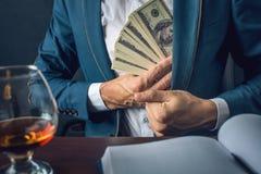 O homem de negócios do homem no terno põe o dinheiro em seu bolso Um subôrno sob a forma das notas de dólar Conceito da corrupção Fotografia de Stock Royalty Free
