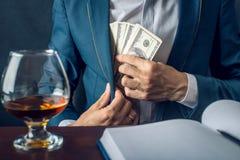 O homem de negócios do homem no terno põe o dinheiro em seu bolso Um subôrno sob a forma das notas de dólar Conceito da corrupção Imagem de Stock Royalty Free