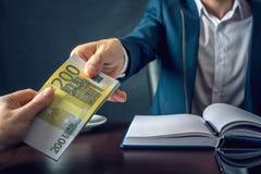 O homem de negócios do homem no terno toma as mãos do dinheiro Um subôrno sob a forma das contas do Euro Conceito da corrupção e  Imagens de Stock Royalty Free