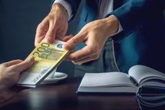 O homem de negócios do homem no terno toma as mãos do dinheiro Um subôrno sob a forma das contas do Euro Conceito da corrupção e  Foto de Stock Royalty Free