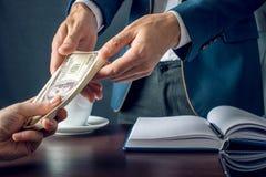 O homem de negócios do homem no terno toma as mãos do dinheiro Um subôrno sob a forma das notas de dólar Conceito da corrupção e  Fotos de Stock Royalty Free