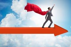 O homem de negócios do super-herói que está na seta imagens de stock royalty free