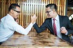 O homem de negócios dois expressou uma expressão séria e a luta pela luta romana de braço usada na tabela de madeira imagens de stock royalty free