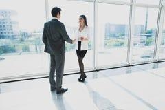 O homem de negócios de dois jovens e a mulher de negócio estão estando no escritório moderno com janelas panorâmicos Fotografia de Stock Royalty Free