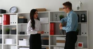 O homem de negócios e a mulher de negócios comunicam o armário próximo ereto com os dobradores
