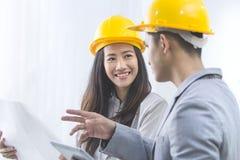 o homem de negócios e a mulher de negócios com modelo e os capacetes discutem Imagens de Stock Royalty Free