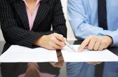 O homem de negócios e a mulher de negócios estão apontando ao artigo do tr imagens de stock