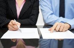 O homem de negócios e a mulher de negócios estão inspecionando o contrato fotos de stock royalty free