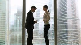 O homem de negócios e a mulher de negócios que encontram-se perto da janela do escritório, mulher estão atrasados vídeos de arquivo