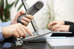 O homem de negócios e a mulher estão contactando clientes novos sobre o telefone Imagem de Stock Royalty Free