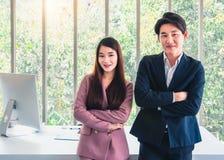 O homem de negócios e a mulher de negócios na posição do terno convidam todos para juntar-se na equipe fotos de stock royalty free