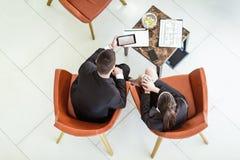O homem de negócios e a mulher de negócios que sentam-se nas poltronas reveem a documentação, vista superior fotografia de stock royalty free