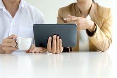 o homem de negócios e a mulher de negócios sentam o mercado do presente da tabuleta do uso do trabalho Imagens de Stock Royalty Free