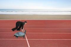 O homem de negócios e a tartaruga estão prontos para competir na pista de atletismo foto de stock