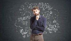 O homem de negócios em calças de brim marrons está pensando sobre o negócio novo Foto de Stock