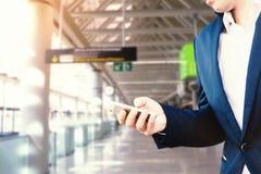 O homem de negócios em um casaco azul e em uma camisa branca no aeroporto guarda um smartphone em sua mão imagem de stock