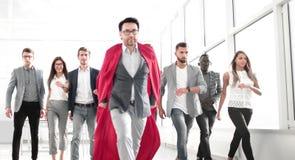 O homem de negócios em um casaco do ` s do super-herói é antes da equipe do negócio imagem de stock royalty free